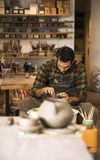 Male artist makes clay pottery on a spin wheel. View at an artist makes clay pottery on a spin wheel stock image