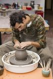 Artist makes clay pottery on a spin wheel in workshop. View at an artist makes clay pottery on a spin wheel in workshop stock photos
