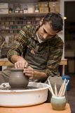 Artist makes clay pottery on a spin wheel in workshop. View at an artist makes clay pottery on a spin wheel in workshop royalty free stock image