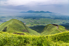 View of Aso volcano mountain and farmer village from hill top in Royalty Free Stock Image