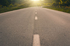 View of asphalt road, blue sky and sun. Royalty Free Stock Image