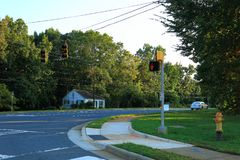 View of an asphalt road with stoplights and green trees on blue sky background. North Carolina. September, 2017 Stock Image