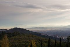 View of Assisi town from behind, with Francis church and Fortress above an hill full of autumn trees royalty free stock photos