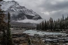 A view at Athabasca Falls. Autumn at Athabasca falls , just after a light snowfall . The water still flowing and the clouds are rolling in stock image