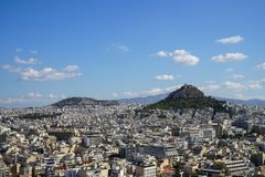 View of Athens city from Acropolis showing white buildings architecture, Mount Lycabettus, blue sky and floating white cloud Stock Image