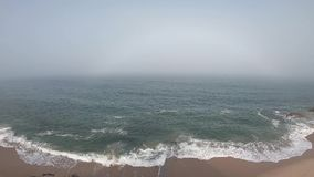 View of the Atlantic Ocean. Empty beach in Povoa de Varzim, Portugal on foggy autumn day with waves crashing on shore. Below and fog in distance stock footage
