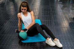 Young fitness girl does abs exercises with a ball in gym. View of attractive fit girl exercising with ball on floor of modern gym stock photo