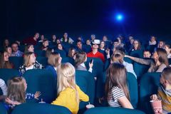People looking at boy wearing virtual glasses in movie theatre. View of audience watching film in movie theatre. Boy in virtual glasses sitting in centre Stock Photos
