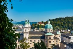 View of the Austrian city of Salzburg and the Dome church, with. Other buildings, mountains and forest under blue sky stock images
