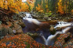 View into autumn mountain river with blurred waves, fresh green mossy stones and boulders on river bank covered. stock photography