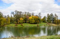View of an autumn park with colorful leaves. And a pond in the foreground Royalty Free Stock Photography