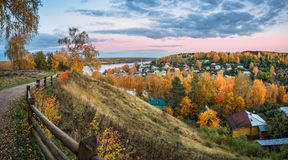 View of the autumn town of Plyos through the wooden fence. Of the Cathedral Mountain on a warm evening royalty free stock photos