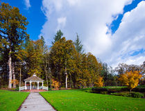 View of autumn trees and clearing path to wood gazebo. Elegant gazebo in a beautiful autumn park with yellowed trees and flat track, cut surface of green grass Royalty Free Stock Photography