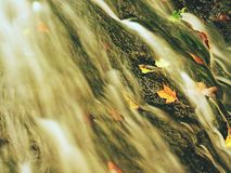 Autumn waterfall in basalt rock. Shinning streams and many colorful leaves on banks. View into autumn waterfall in basalt rock. Shinning streams and many Royalty Free Stock Photo