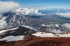 View from Avachinsky volcano to Koryaksky volcano, Kamchatka. In august. The weather is good. The Avachinsky volcano is active and it has the red color of Stock Photo
