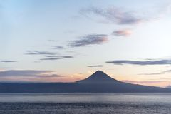 Azores - View over water to the volcano Pico in the evening light royalty free stock images