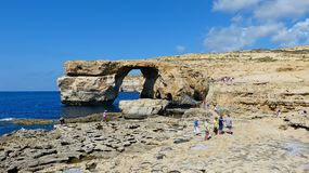 View of the Azure Window in Malta. Dwejra, Malta – September 26, 2013. View of the Azure Window in Malta, from a distance, with people. The thrilling coastline Royalty Free Stock Photo