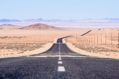 View of the B4 road between Lüderitz and Keetmanshoop near Garub in Namibia, Africa. The road cuts through the famous Namib Desert. Mountains in the Royalty Free Stock Image