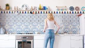 View from the back of beautiful young woman with blond hair in white t-shirt and blue jeans polishing the table in the stock image