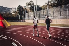 View from the back of a black man and a white man run on a turn royalty free stock photography
