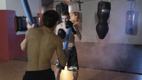 View from the back of the coach. The sportsman the boxer fulfills blows before fight. Boxing training in gloves. The stock video