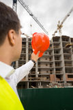 View from back on construction engineer pointing at building sit Stock Photo