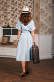 View from the back of female with suitcase. Young female standing in the room with suitcase, view from the back. Vintage travel waiting concept. Retro style Royalty Free Stock Photos