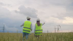 The view from the back: group of engineers at a high-voltage power plant with a tablet and drawings walk and discuss a stock footage