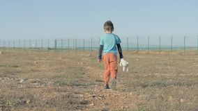 View from the back of juvenile child leaving moving towards Mexican border. Unhappy Abandoned Lonely boy walk with her Friend Tedd. Y bunny Toy desert terrain on stock video footage