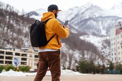 View from back. Man tourist in yellow hoodie, cap with backpack stands on background of high snowy mountains and using smartphone stock photos
