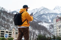View from back. Man tourist in yellow hoodie, cap with backpack stands on background of high snowy mountains and using smartphone royalty free stock photo