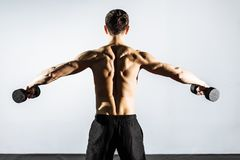 The view from the back. Muscular man doing exercises with dumbbells.  Royalty Free Stock Photo