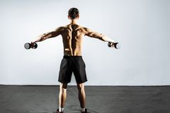 The view from the back. Muscular man doing exercises with dumbbells.  Stock Photos