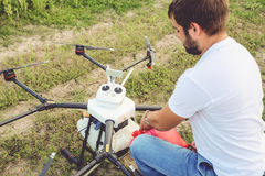 View from the back process of preparing agro drones for irrigation. A man agronomist pours liquid into a Octocopter stock photos