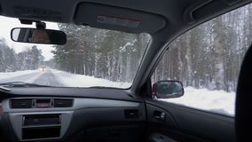 View from back seat car moving on winter road. Woman driver driving in snowy road stock video footage