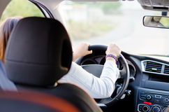 Woman driving a car. View from the back seat of a woman driving a car with focus to her hands on the steering wheel and with the seat rest obscuring her head Royalty Free Stock Photos
