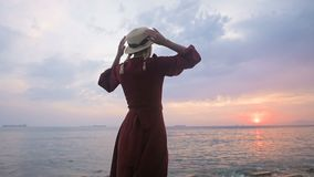 The view from the back. Slow motion Portrait of a young girl in a red dress and a straw hat on the seashore against a. Rocky shore and pink sunset. A girl in stock footage