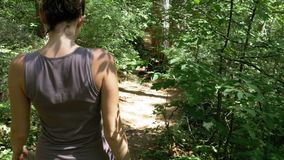 View from the back to traveler woman hiking on the forest trail path in mountain. Walking on Rocks. The camera behind the girl moves smoothly. Achieving the stock video