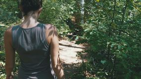 View from the Back to Traveler Woman Hiking on the Forest Trail Path in Mountain. Walking on Rocks. The camera behind the girl moves smoothly. Achieving the stock footage