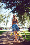 View from the back woman bicycling posing with a yellow retro bicycle. stock photos