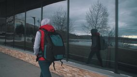 Girl in red sleeveless jacket walks next to the large windows on cloudy day. stock video footage
