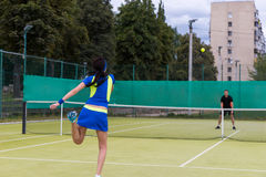 View from the back on a young female tennis player serving durin Royalty Free Stock Image