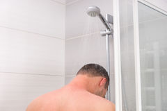 View from the back on a young man taking a shower. And standing under flowing water in the modern tiled bathroom Royalty Free Stock Photography