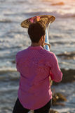 View from the back young musician play the trumpet on rocky sea coast during surf. Stock Photo