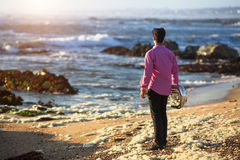 View from the back young musician play trumpet on rocky sea coast during surf. Stock Photography