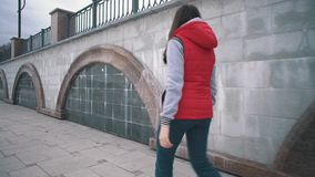 Girl in sleeveless red jacket walks next to marble walls on cloudy day. stock video
