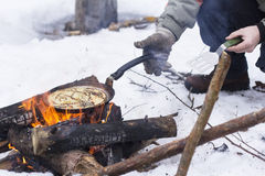 View background people bake pancakes on a fire in the open air on a holiday Maslenitsa. View background people bake pancakes on a fire in the open air in the Stock Photos