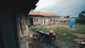 View of the backyard of a house in a deserted poor village. Chickens are walking around the yard. No people. Motorcycle is parked. Clothes, laundry is dried on royalty free stock image