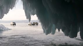 View of the Baikal ice and the excursion cars standing on it from the ice cave with long icicles.  royalty free stock images