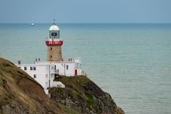 View of The Baily Lighthouse on the Howth peninsular cliffs with a second illuminated lighthouse in the Irish Sea stock images